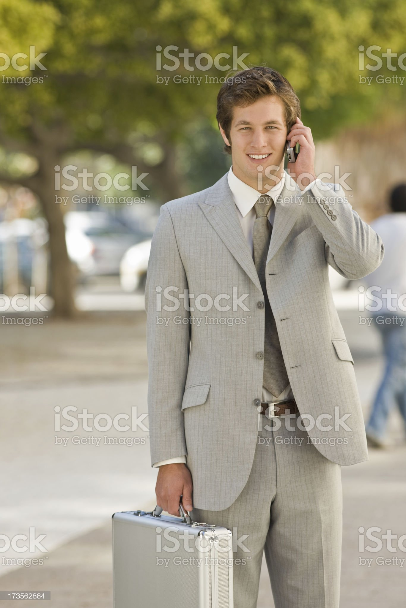 Portrait of a smiling young businessman talking on mobile phone royalty-free stock photo