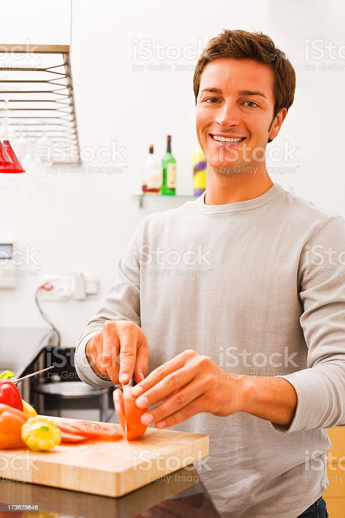 Portrait of a smiling young man cutting vegetables in kitchen royalty-free stock photo