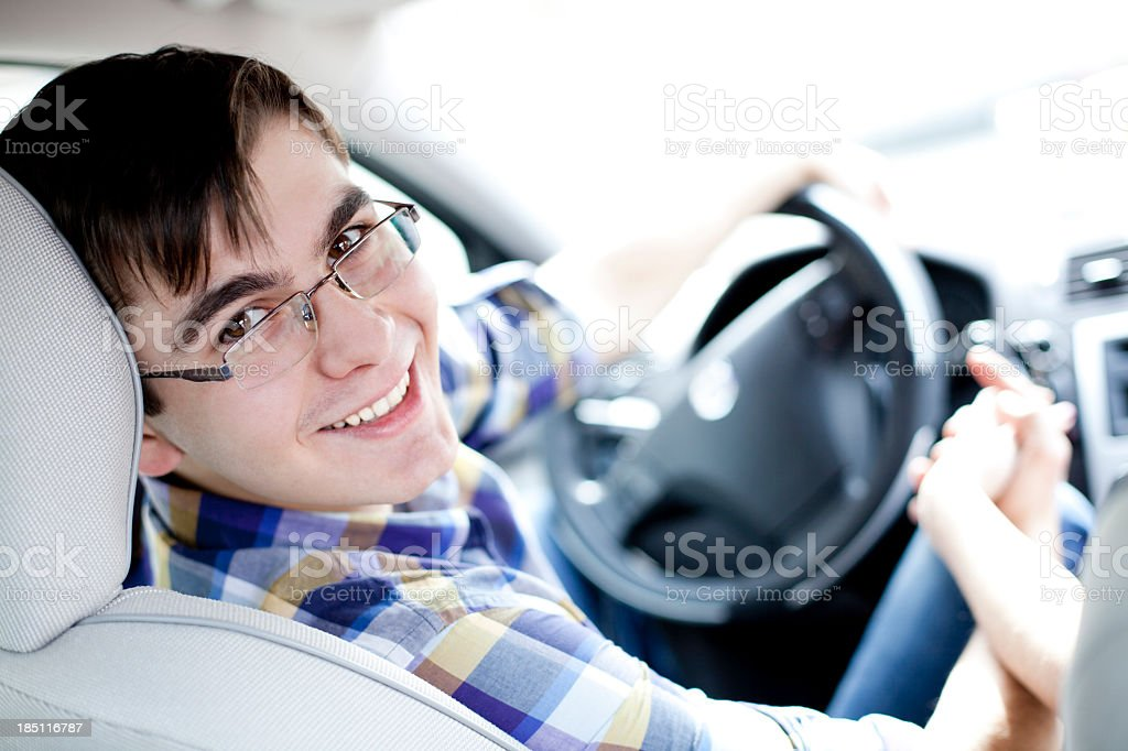 Portrait of a smiling young man driving car stock photo