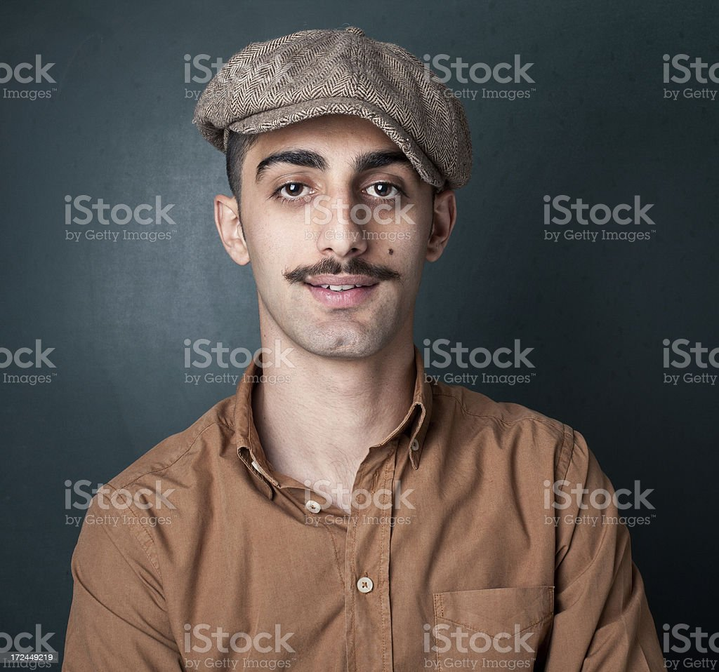Portrait of a Smiling Young Man in a Newsboy Cap stock photo