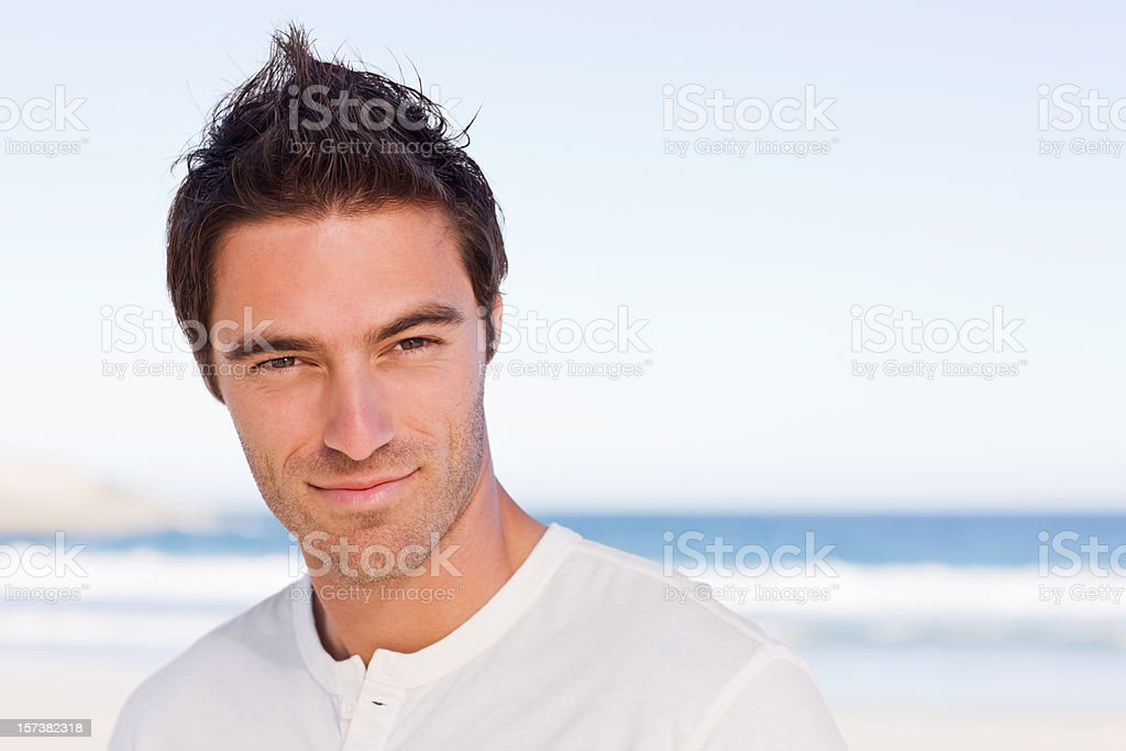 Portrait of a smiling young man on beach royalty-free stock photo