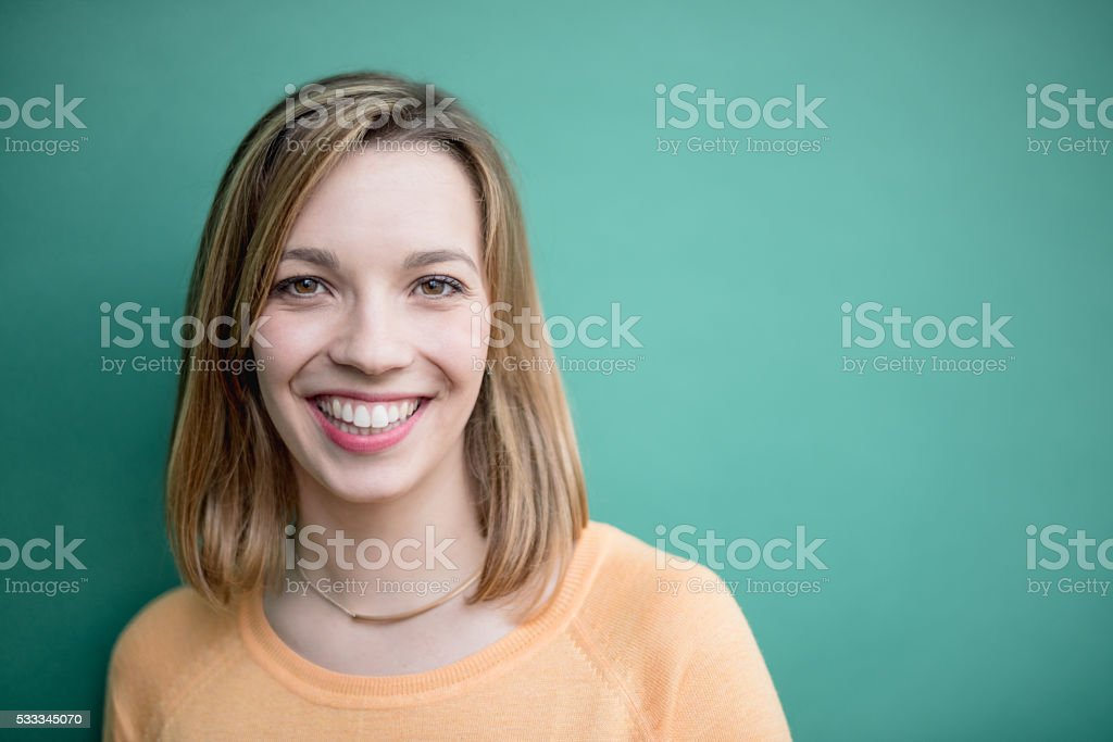 Portrait of a smiling young woman on green stock photo