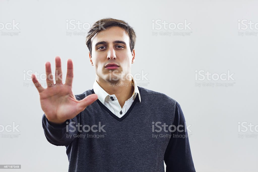 Portrait of a stern man with hand facing out in a stop sign stock photo