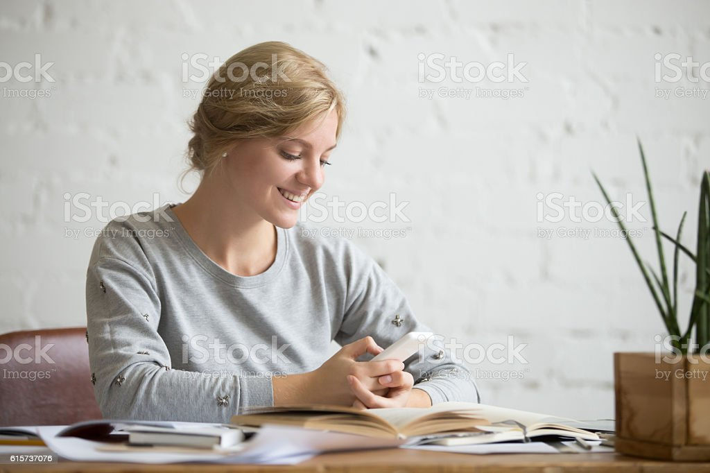 Portrait of a student girl at the desk with phone stock photo