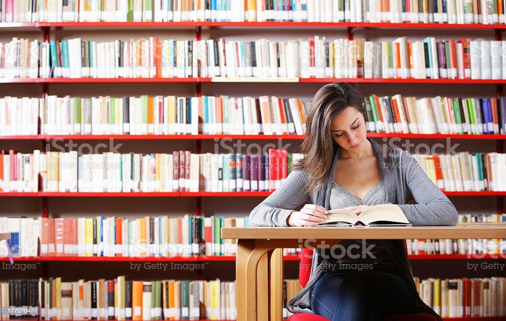 Portrait d'un étudiant de fille étudier dans la bibliothèque photo libre de droits