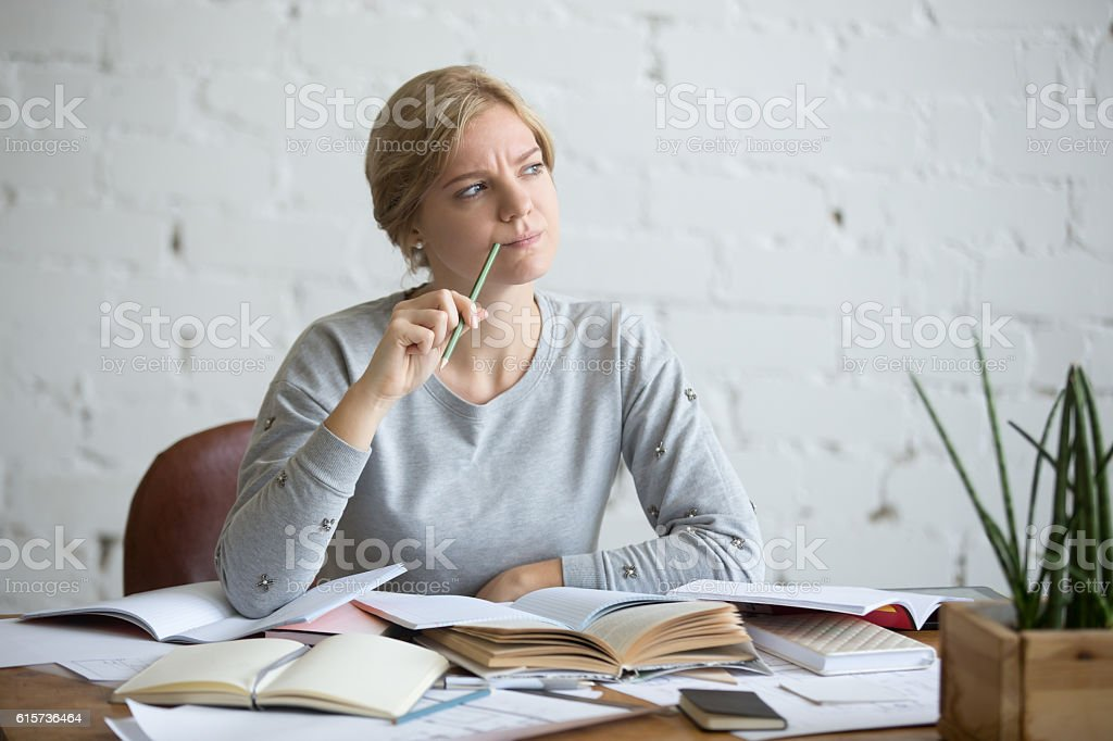 Portrait of a student woman at the desk, frowned stock photo