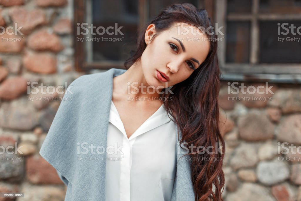 Portrait of a stylish beautiful woman in a gray coat and white blouse against a background of a stone wall stock photo