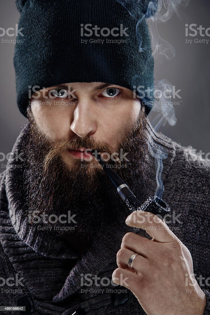 portrait of a stylish man with beard and pipe stock photo