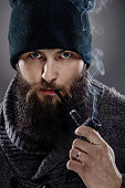 portrait of a stylish man with beard and pipe