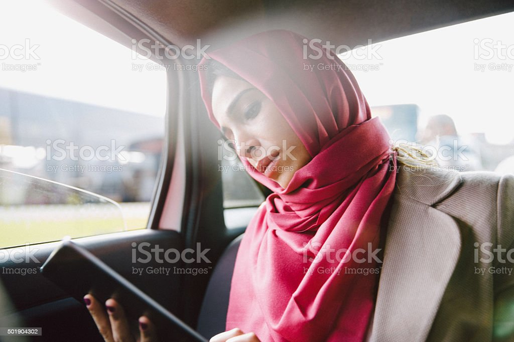 Portrait Of A Successful Businesswoman Using Tablet In A Taxi stock photo