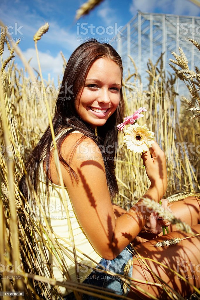 Portrait of a sweet young female with flower at a crop field stock photo