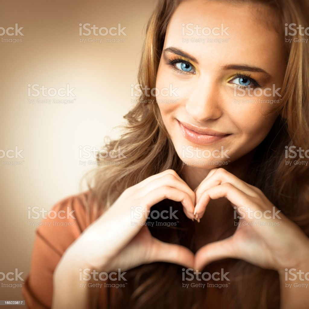 Portrait of a teen girl making a heart shape with her hands royalty-free stock photo