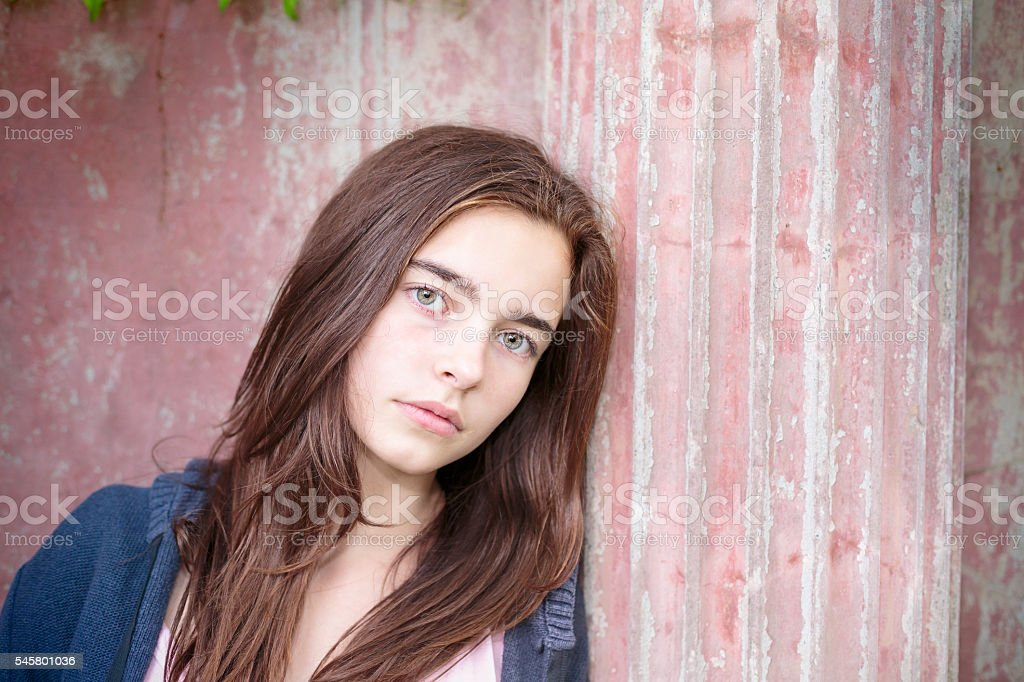 portrait of a teenage girl, leaning against an ancient pillar stock photo
