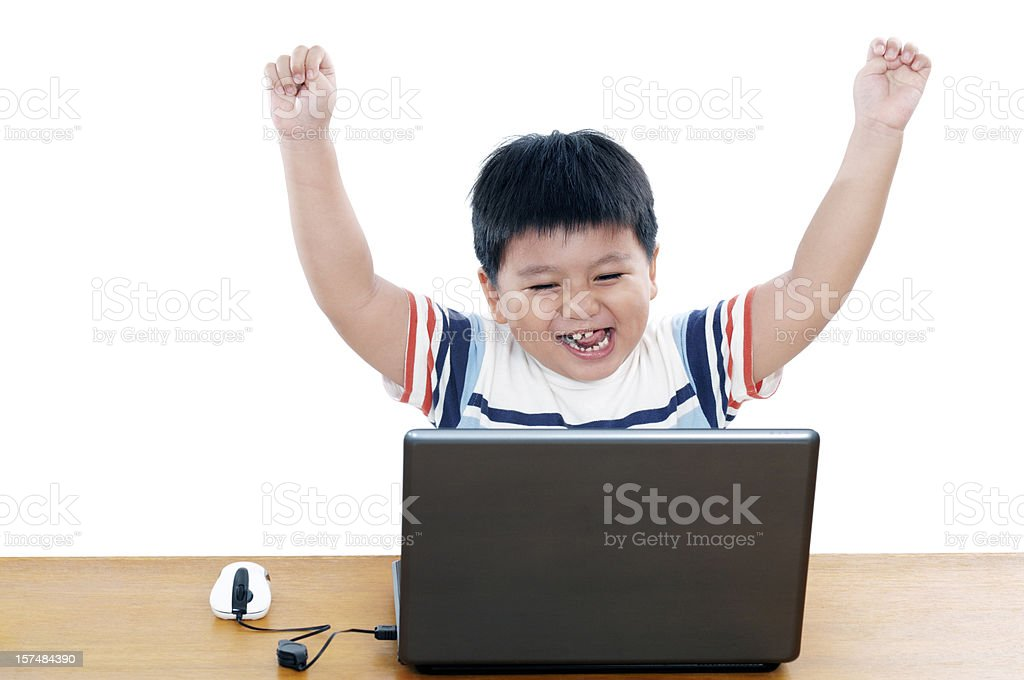 Portrait of a thrilled young boy with his laptop stock photo