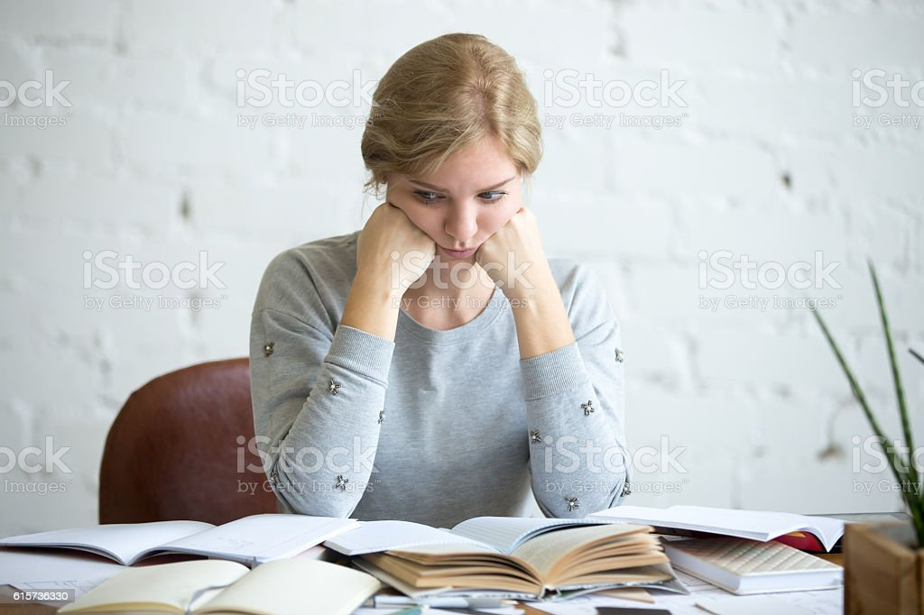 Portrait of a tired student woman at the desk stock photo
