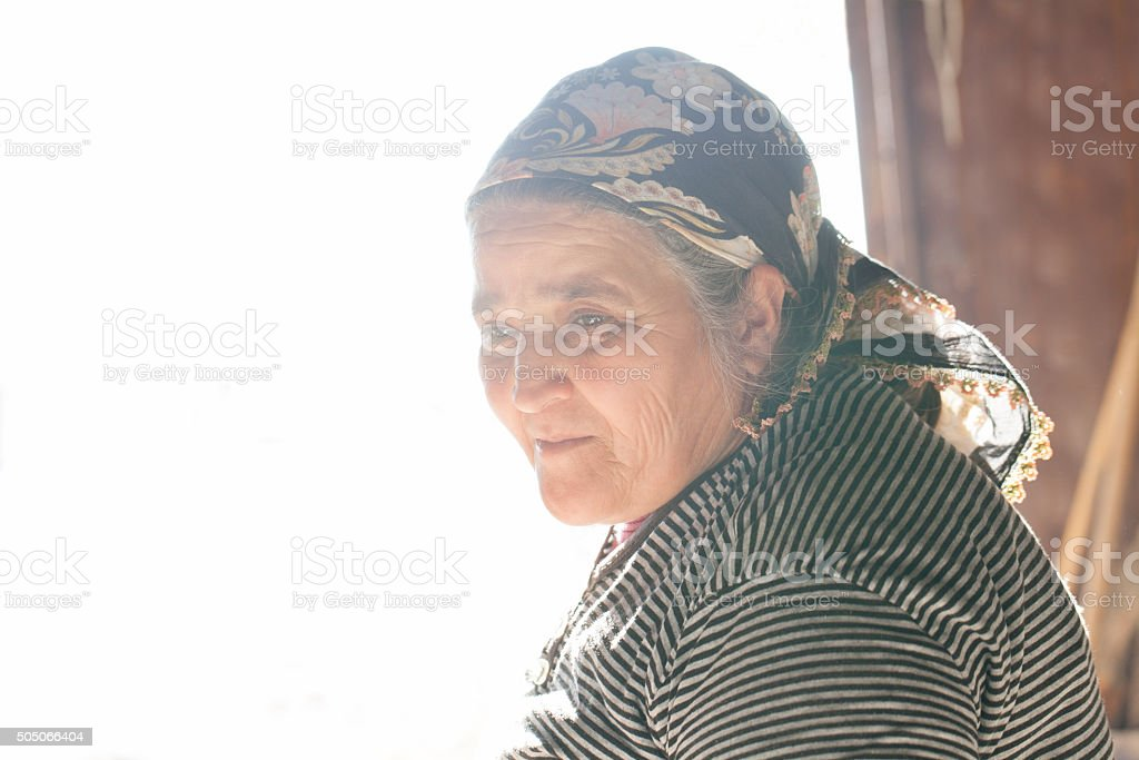 Portrait of a turkish old woman in a backlit stock photo