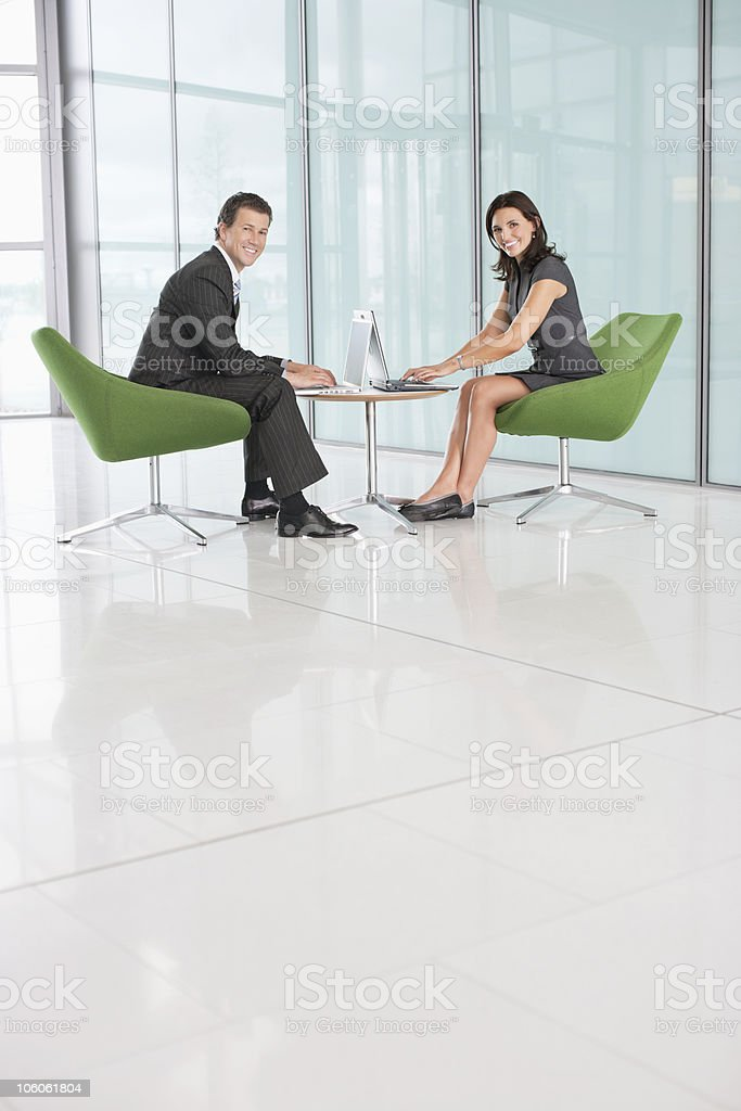 Portrait of a two smiling business executives working laptop royalty-free stock photo