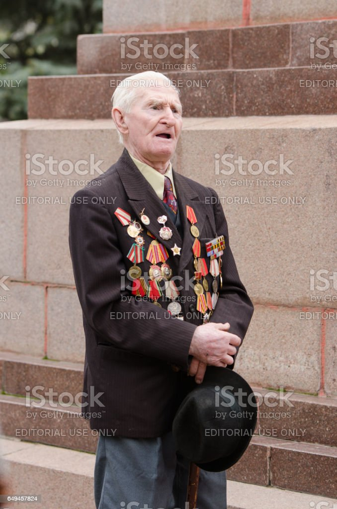 Portrait of a veteran on  background monument to fallen stock photo