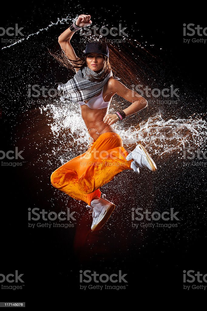 Portrait of a woman dancing in mid air with sprayed water stock photo