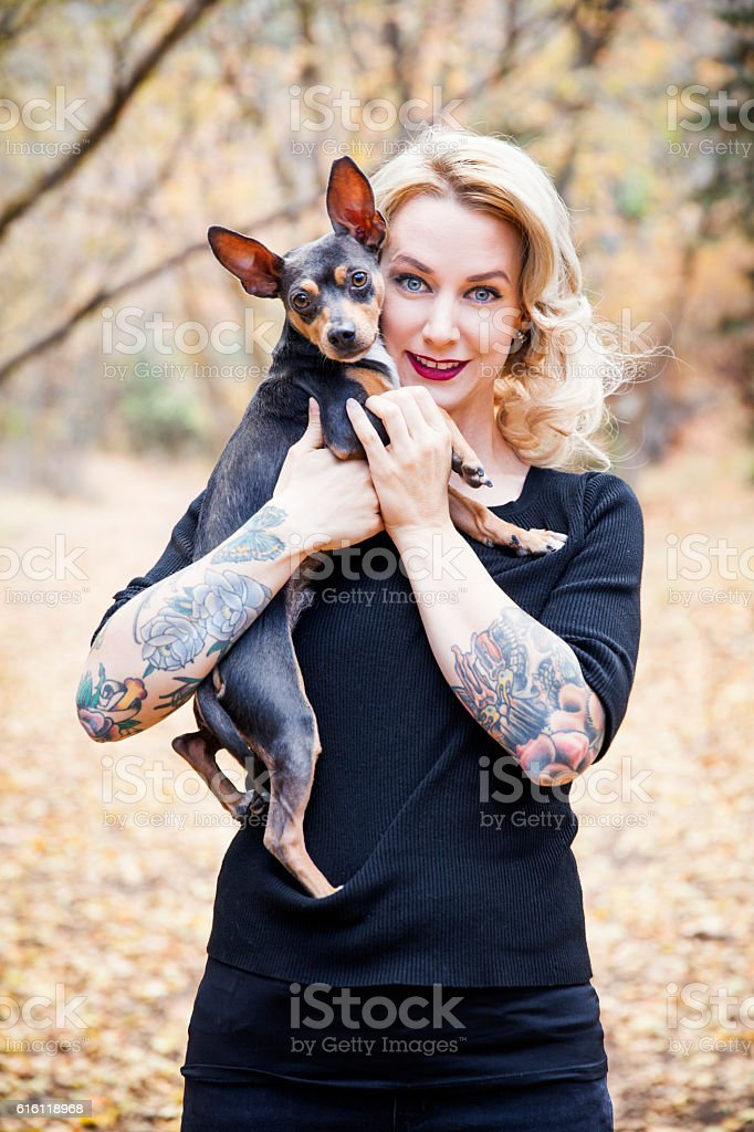 Portrait of a Woman Holding Her Dog Outside stock photo