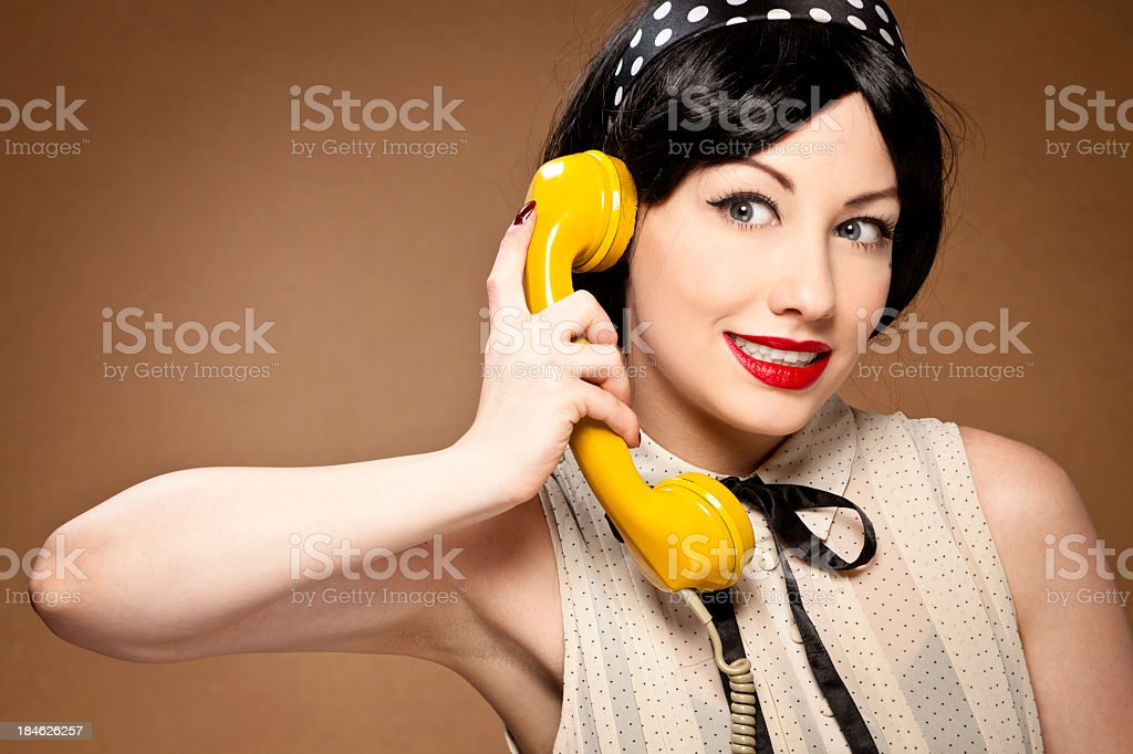 Portrait of a woman in red lipsticks holding a yellow phone royalty-free stock photo