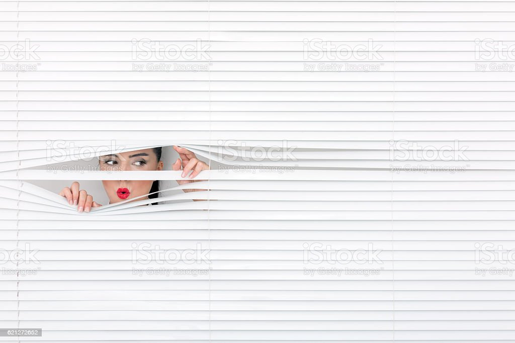 Portrait of a woman looking through out the blinds. stock photo