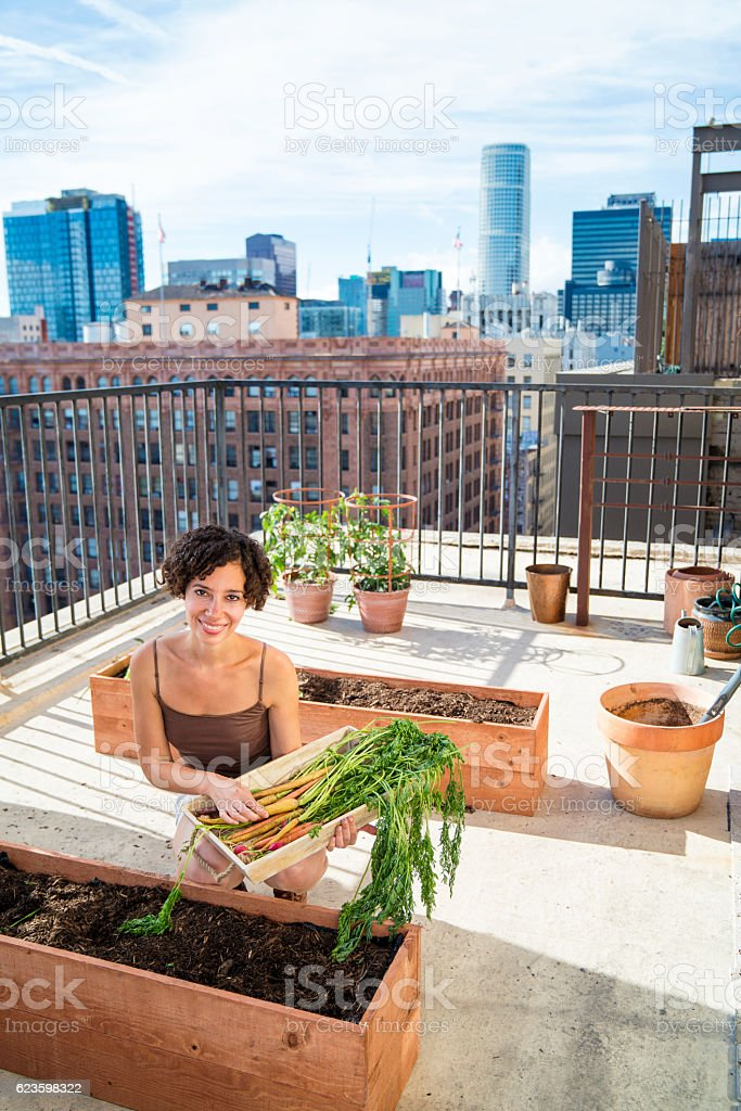 Portrait of a woman tending to her rooftop garden stock photo