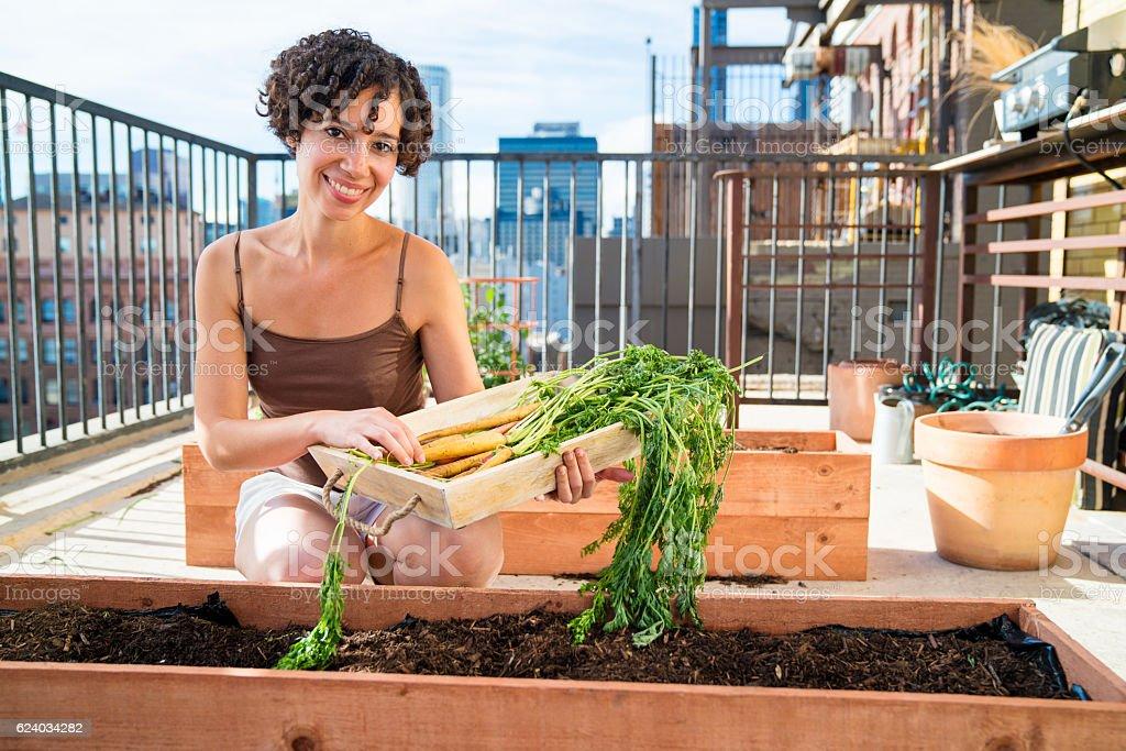 Portrait of a woman tending to her urban garden stock photo