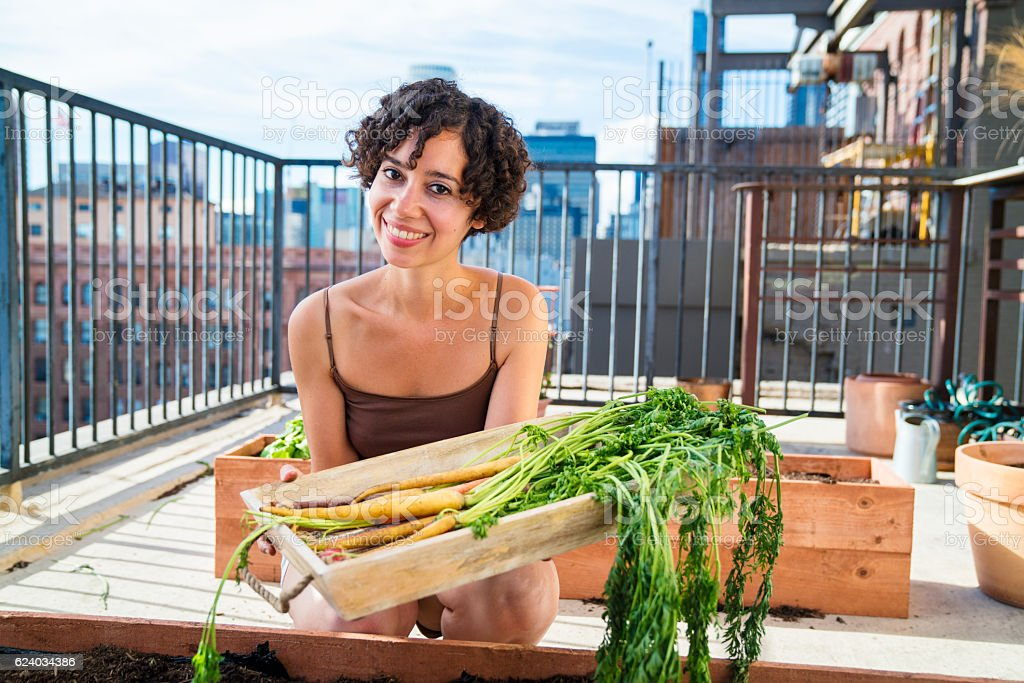 Portrait of a woman tending to her urban garden stock photo