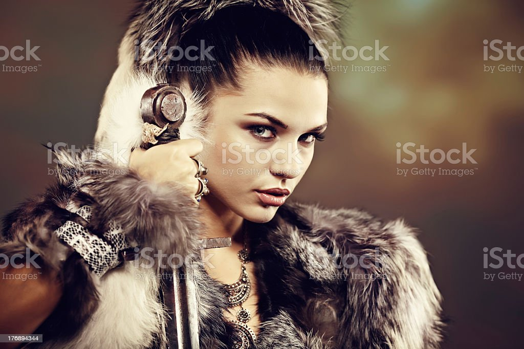 Portrait of a woman wearing furs and holding a sword stock photo