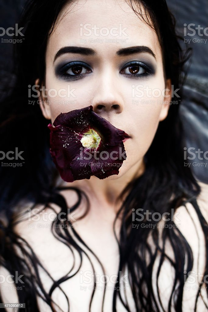 Portrait of a woman with a flower in her mouth stock photo