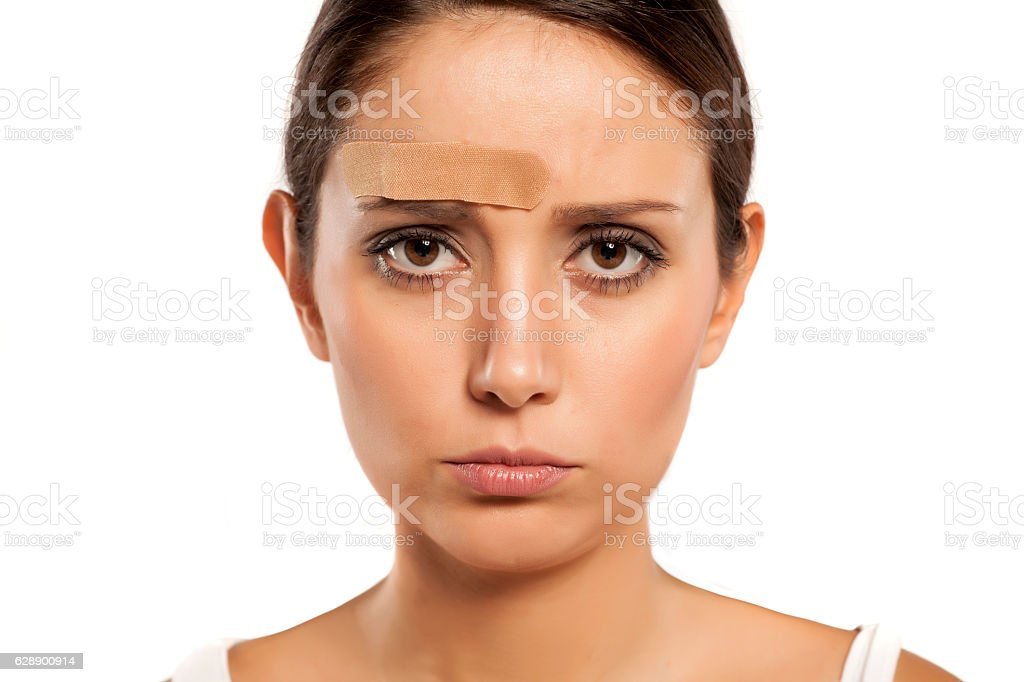 portrait of a woman with a plaster above her eybrow stock photo