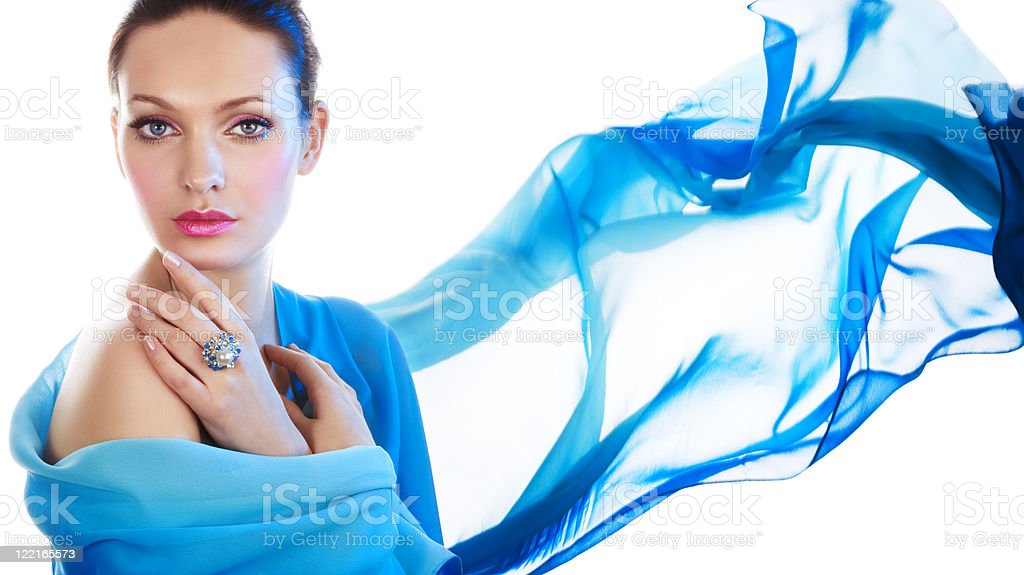 A portrait of a woman with blue fabric blowing away stock photo