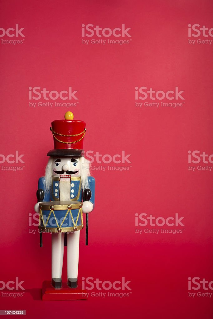 Portrait of a wooden nutcracker on light red background stock photo