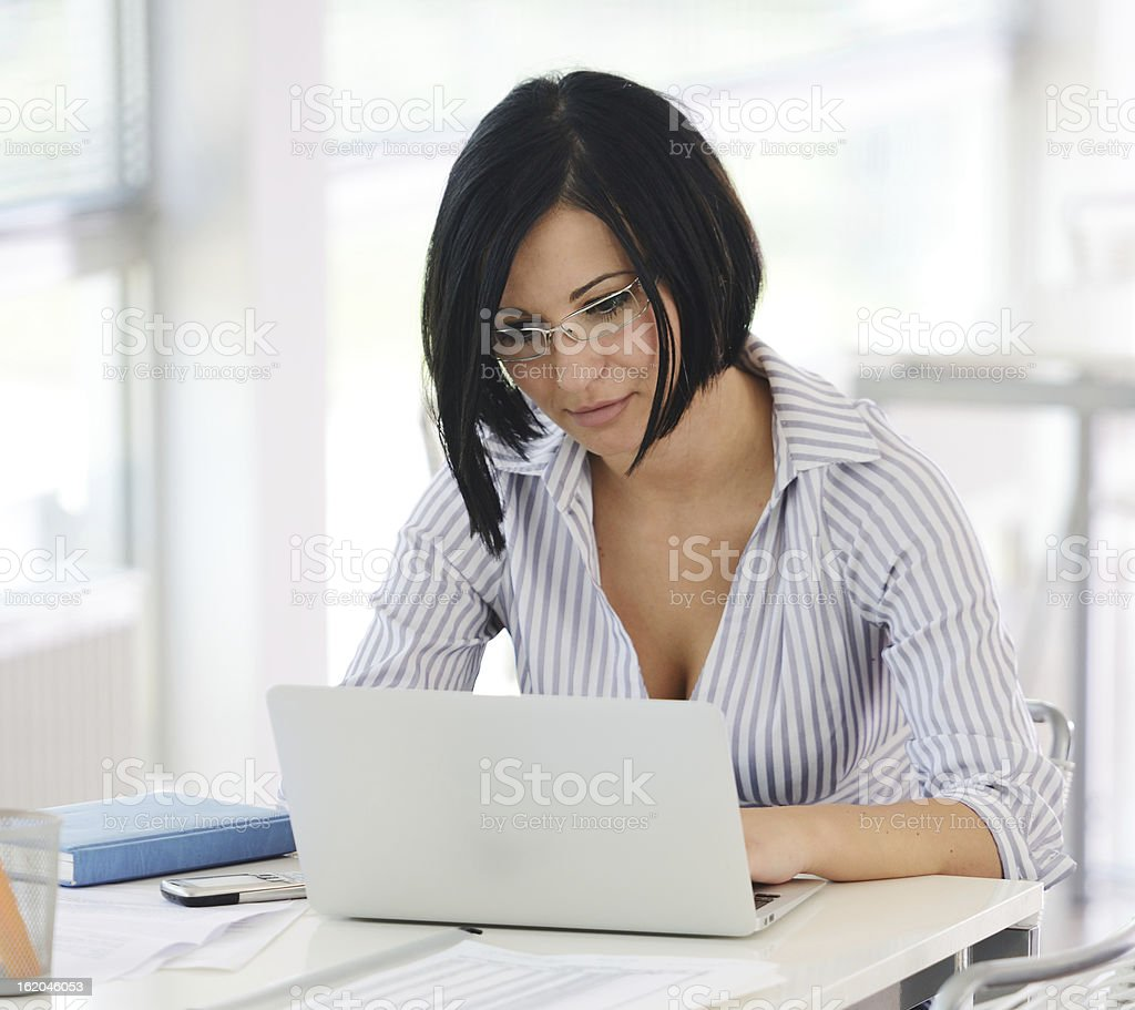 Portrait of a working businesswoman sitting at her desk royalty-free stock photo