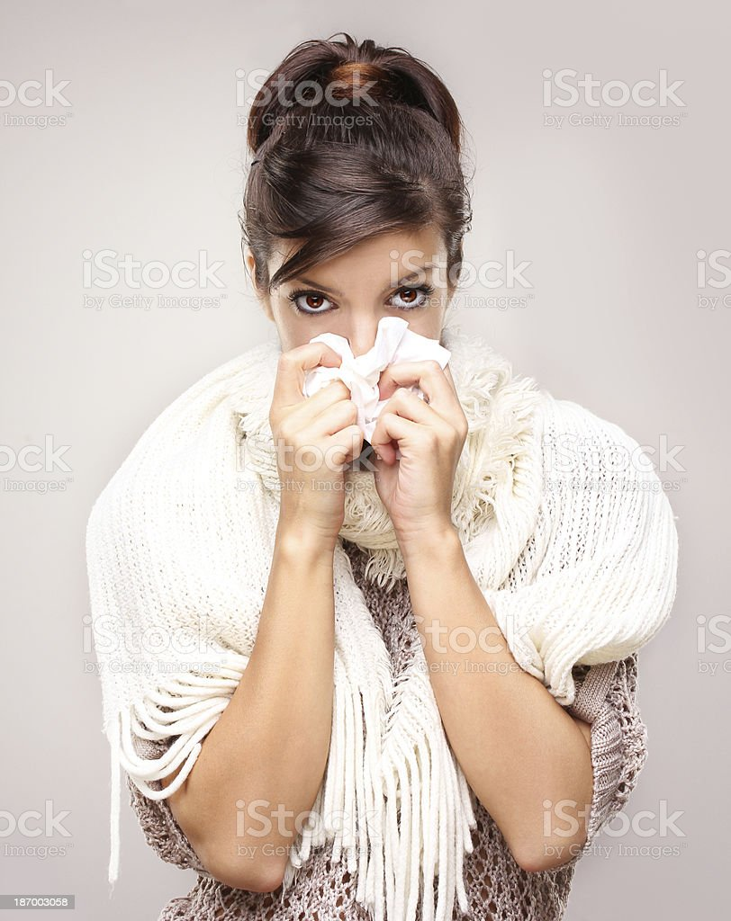 Portrait of a young adult woman blowing nose. stock photo