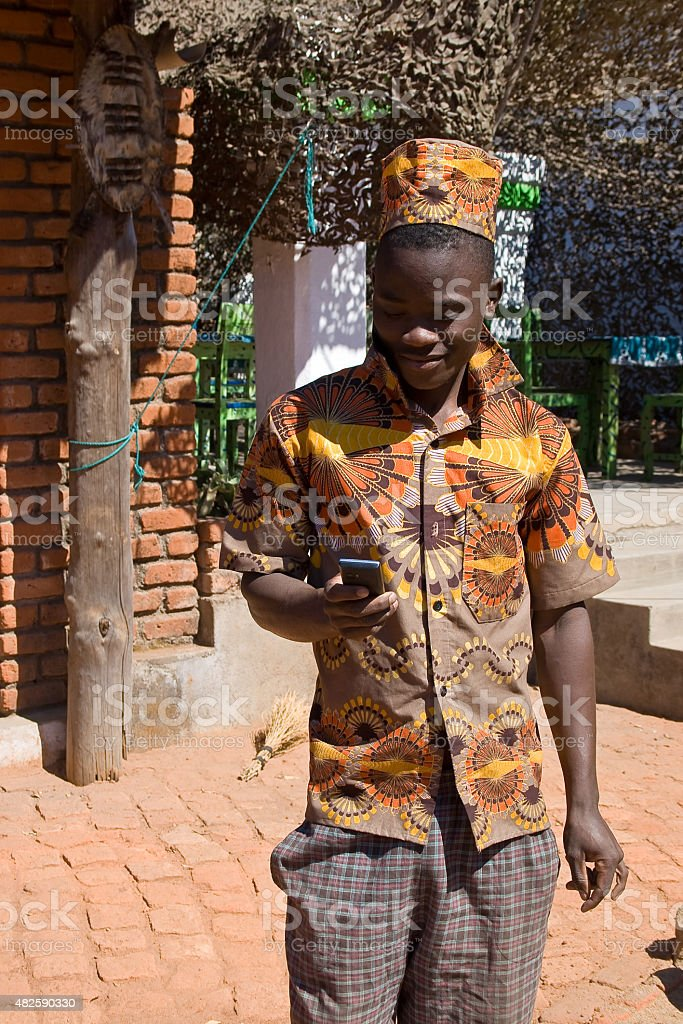 Portrait of a young African man looking at mobile phone. stock photo