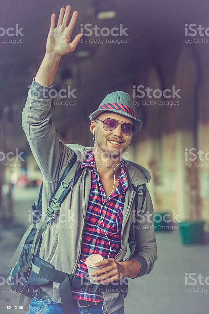 Portrait of a young Backpacker waving on the train station stock photo