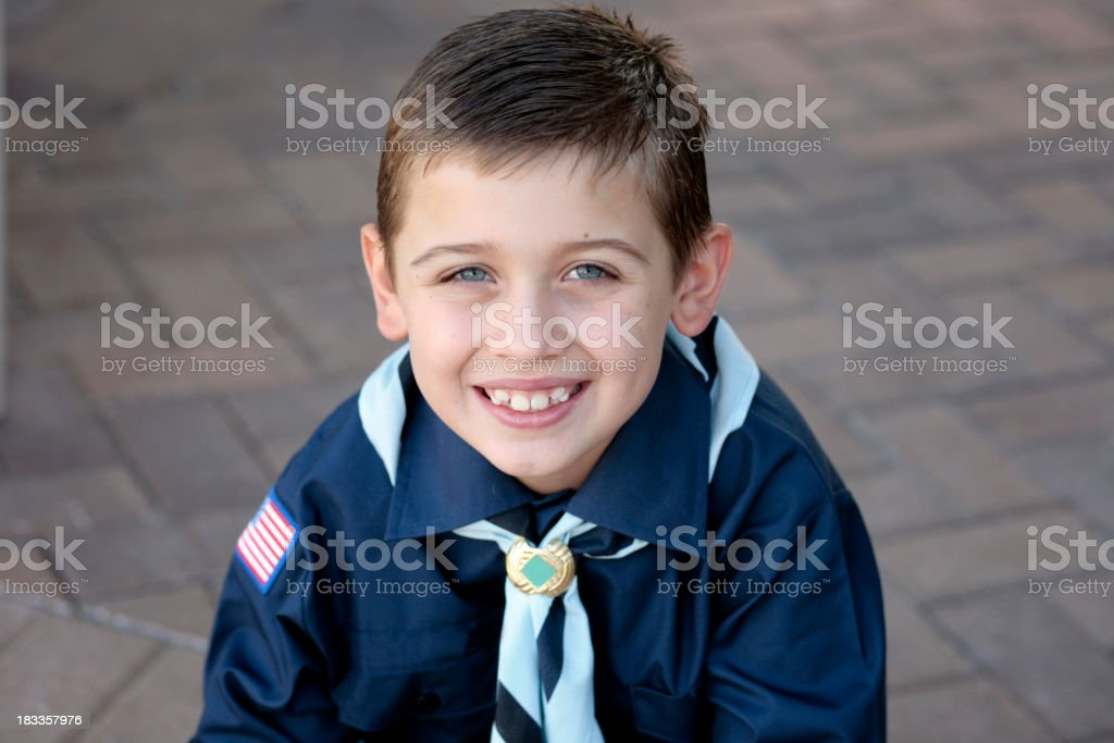 Portrait of a young boy scout in blue uniform smiling royalty-free stock photo