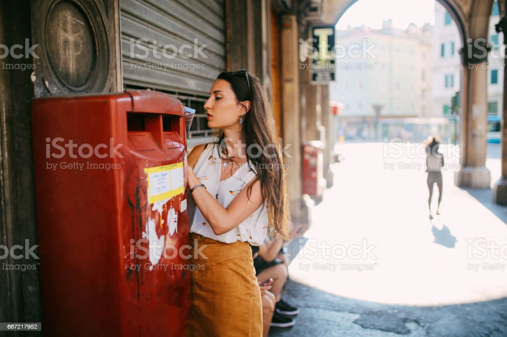 Portrait of a young brunette in Trieste, Italy writing a postcard stock photo