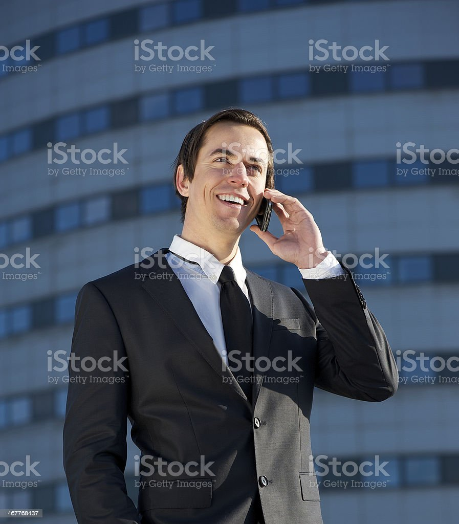 Portrait of a young business man talking on cellphone outdoors royalty-free stock photo