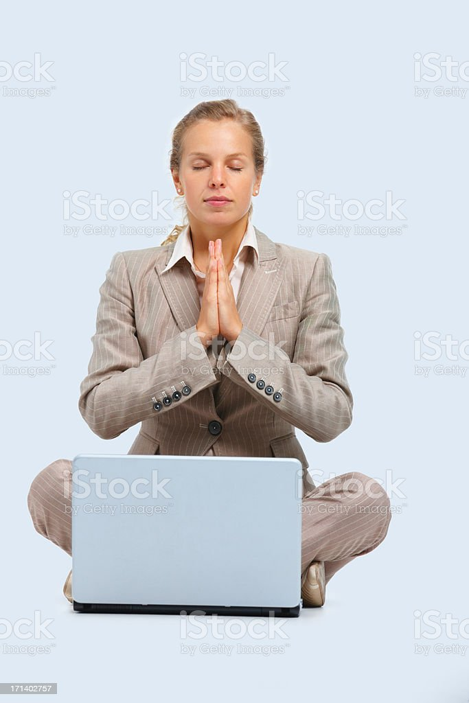 Portrait of a young business woman praying with a laptop royalty-free stock photo