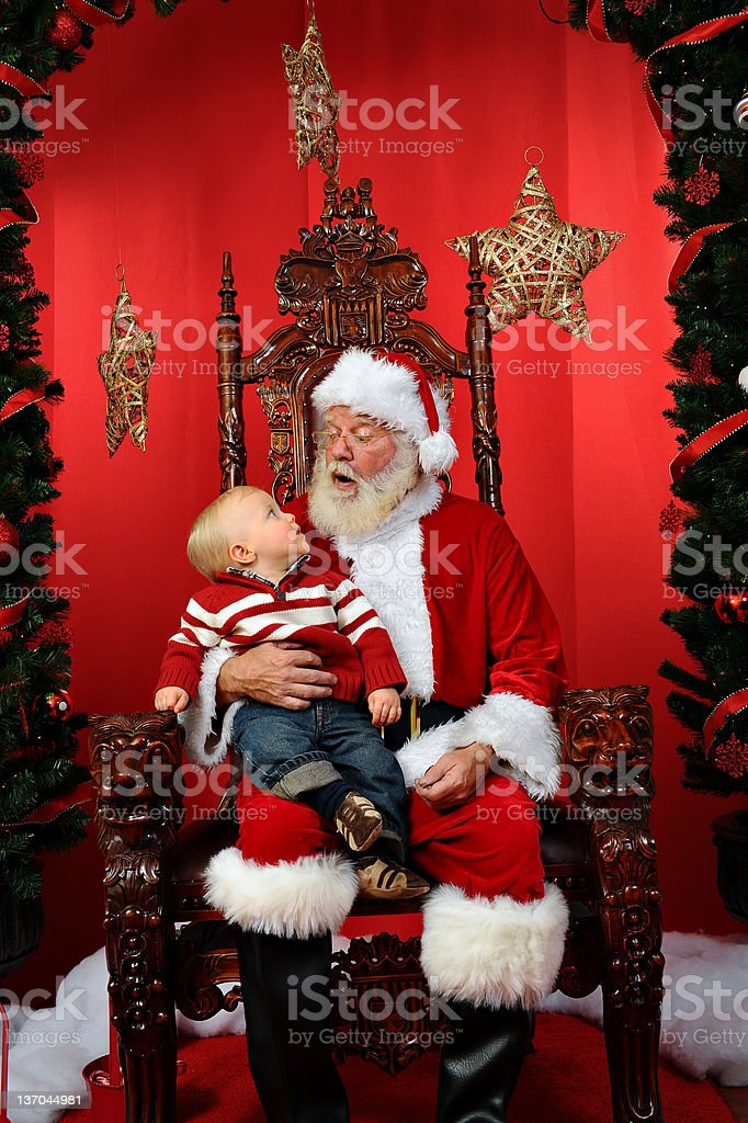 Portrait of a young child sitting on Santa Claus' lap stock photo