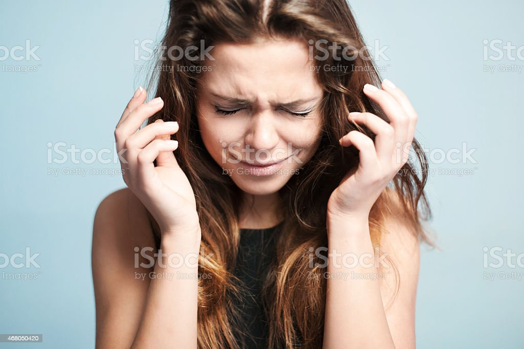 Portrait of a young crying woman on a pale blue background stock photo
