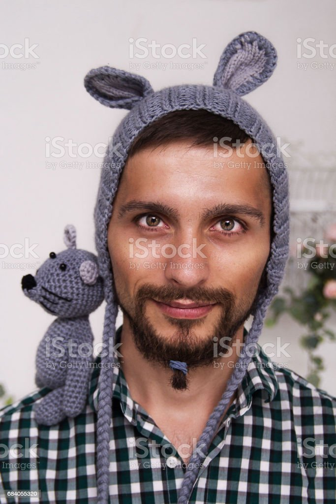 Portrait of a young daddy in a children's hat with ears and a mouse on his shoulder stock photo