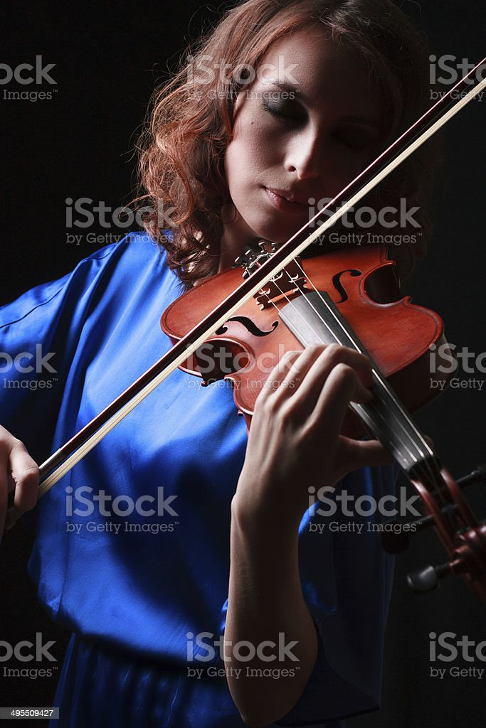Portrait of a young female playing the violin stock photo