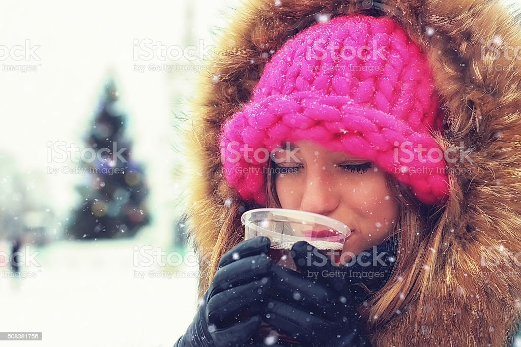 portrait of a young girl in the winter drink wine stock photo