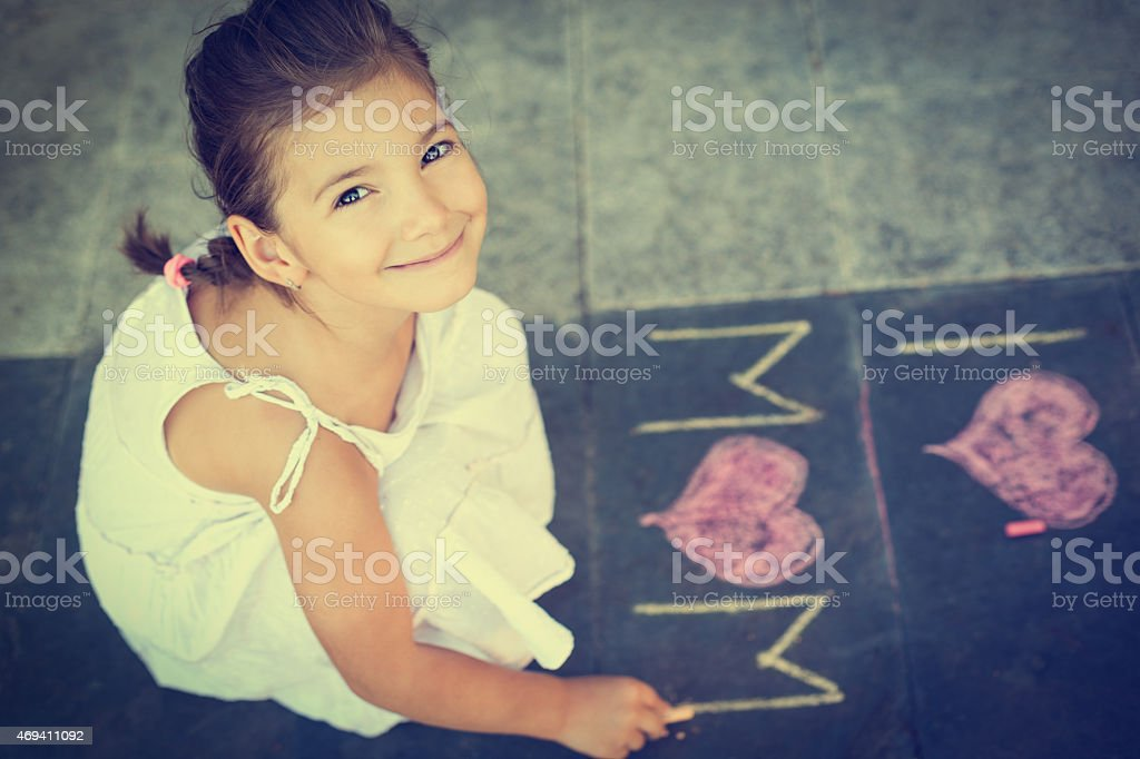 Portrait of a young girl playing with sidewalk chalk stock photo