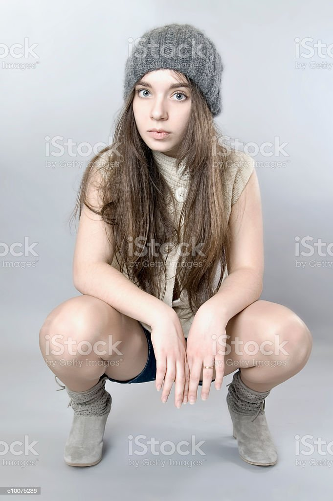 Portrait of a young girl sitting on his haunches. stock photo