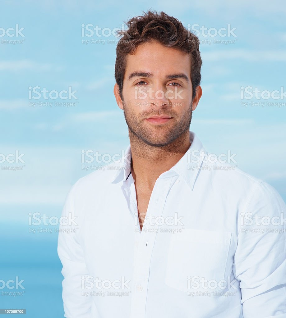 Portrait of a young guy smiling against natural background royalty-free stock photo